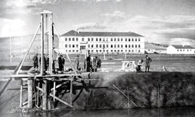 <p><strong>10. </strong>Çifteler Köy Enstitüsü'nün Hamidiye kolundaki Usta  Sili Layoş ve öğrenciler tarafından inşa edilen üç katlı yapı. (Resim 9'da sarı  ile işaretlenmiş yönetim yapısı) Önde Seydi Suyu üzerine köprü inşaatı devam  ediyor.<br />Kaynak: Düşünen  Tohum Konuşan Toprak, İsmail Hakkı Tonguç Belgeliği </p>