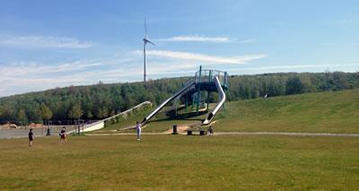 <p><strong>12.</strong> Tepede yenilenebilen enerji kaynağı olarak rüzgar  türbini, ön tarafında Bergparkta çocuk oyun alanı<br />Fotoğraf: A. D. Kaçar</p>