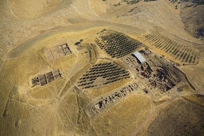 <p><strong>1. </strong>Göbekli  Tepe Dünya Miras Alanının, 2011 yılında koruyucu çatıların yapımından önce havadan  görünümü. Höyük, yüksek tepelerden ve daha alçak çukurlardan oluşan bir  yerleşim silsilesi sunmaktadır. Ana kazı alanından (güneydoğuda yer alan çukur;  sağda ortada) höyüğün güneybatısı boyunca, batıya doğru yayılan sekiz kazı  alanı yer almaktadır. Höyüğün kuzeybatısında, ilerleyen çalışmaların  gerçekleştirildiği yükselti (solda üstte) ve çukur (solda ortada)  bulunmaktadır.</p>