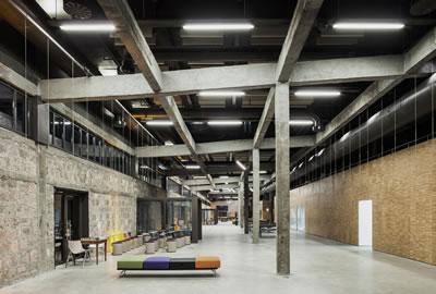 <p><strong>12b. </strong>Fabrika yapısının yeni yapı içinden görünen izleri<br />Fotoğraf: Studio Majo</p>