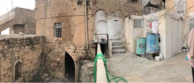 <p><strong>Resim  1.</strong> Geleneksel taş  yapılaşmaya kullanıcısı tarafından eklenmiş betonarme balkon, merdiven, tuvalet+su  deposu ekleri</p>