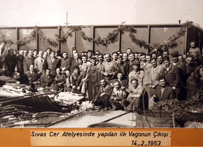 <p><strong>18. </strong>Cer Atelyesi ilk kapalı vagonun çıkışı ve işçiler <br />   Kaynak: TÜDEMSAŞ arşivi</p>