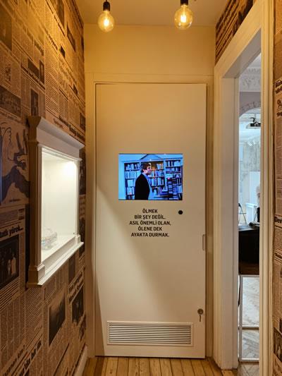 """<p><strong>4.</strong> Koridorda Hrant Dink videosu, """"Ölmek bir şey değil. Asıl  önemli olan, ölene dek ayakta durmak.""""<strong></strong></p>"""