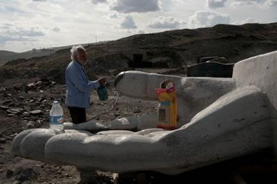 <p><strong>4.</strong> Mehmet Aksoy İnsanlık Anıtı'nın el  parçası üzerinde çalışırken, Eylül 2009</p>