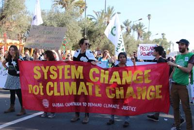 """<p>""""System change, no  climate change"""" (İklim değişikliği değil, sistem değişikliği) yazılı pankart<br />Fotoğraf:  John Englart (CC)</p>"""
