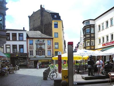 <p><strong>9a. </strong>Löhr  Caddesi&rsquo;nin Münz Meydanı&rsquo;na açıldığı nokta, resmin sağında &ldquo;Pazarcı Kadın ve Zabıta&rdquo;  heykeli görülmekte, solda Münz Meydanı&rsquo;ndaki yeme-içme mekânları <br />Fotoğraflar: D. Darby</p>