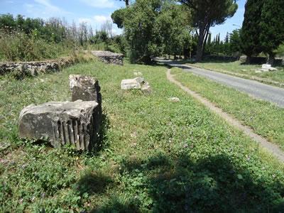 """<p><strong>10.</strong> Via Appianın bugünkü durumu, 2018. Anıtsal  yapı ve mezarların yanı sıra yol boyunca birbirinden bağımsız çok sayıda  arkeolojik taş kalıntısı da bulunmaktadır. Antik yolun yeniden kullanımı için  gerekli tüm müdahale ve değişikliğe ek olarak, yüzyıllar içinde ait oldukları  yerler birçok kez değişmiş olabilecek bu taş eserler de yeniden düzenlenmek  durumunda kalmıştır. Envanterlendiğini ve müzecilik yaklaşımıyla belirli bir  tarihî bağlamda yerleştirildiğini varsayabileceğimiz bu eserler, ölçeği ne  olursa olsun bir """"yorumlama"""" sürecine tabi tutulmuş ve alanın algılanmasını  doğrudan etkileyen """"sunum"""" araçlarına dönüşmüştür.<br /> Fotoğraf:  Mustafa Sayan</p>"""