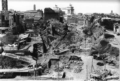 """<p><strong>2.</strong> O zamanki adı ile Via dell'Impero'nun (İmparatorluk Yolu)  açılışı sırasında gerçekleştirilen yıkımlar. Kolezyumun üst katlarından  çekilen bu fotoğrafta, açılmakta olan yolun sonunda (arkada, beyaz) Vittorio  Emanuele Anıtı ve hemen önünde henüz yıkılmamış durumdaki """"Alessandrino"""" semti  görünmekte. Kadrajın ön planında bulunması gereken """"Velia"""" Tepesi ise tamamen  kaldırılmış durumda<br /> Fotoğraf: Luciano Morpurgo, tarihî Kapitol  arşivi (Archivio Storico Capitolino, Biblioteca Romana) </p>"""